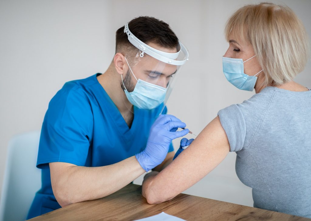Covid-19 vaccination for senior people. Mature woman receiving coronavirus vaccine injection at